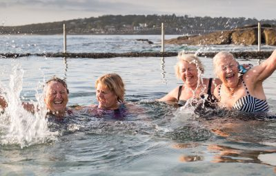 Four ladies from the JellyBean Minstrels laughing, and splashing water about together in the ocean pool Shelly Park Cronulla