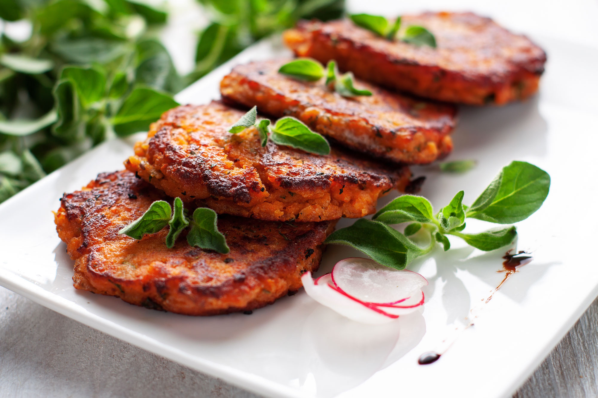 Four palm-sized Salmon Sweet Potato patties resting on a plate garnished with herbs